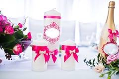 Ślubne świeczki z różowymi faborkami i złotą butelką zdjęcia royalty free