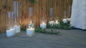 Ślubne dekoracji świeczki z kwiatami i panną młodą w bielu ubierają zbiory