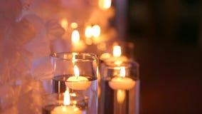 Ślubnej bankiet sala wewnętrzni szczegóły z dekorującym stołowym położeniem przy restauracją Świeczki i biała płatek dekoracja zbiory wideo