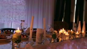 Ślubnej bankiet sala wewnętrzni szczegóły z dekorującym stołowym położeniem przy restauracją Świeczki i biała płatek dekoracja zdjęcie wideo