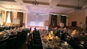 Ślubnej bankiet sala wewnętrzni szczegóły z dekorującym stołowym położeniem przy restauracją Świeczki i biała płatek dekoracja zbiory