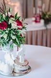 Ślubnej ceremonii dekoracja w restoraunt Skład czerwieni i menchii kwiaty, zieleń stojaki na stole z białym tablecloth, w Fotografia Royalty Free