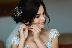 Ślubni kolczyki na żeńskiej ręce są ubranym, ona biorą kolczyki pann młodych opłaty, ranek panna młoda, kobieta w biel sukni obraz royalty free