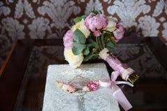 Ślubni złociści pierścionki i bukiet kwiaty na ciemnym drewnianym stole Pojęcia małżeństwo obraz royalty free