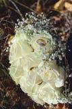 Ślubni złociści pierścionki kłamają na bukiecie białe róże, w górę fotografia stock
