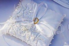 Ślubni złociści pierścionki na białej poduszce Zdjęcia Royalty Free