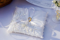 Ślubni złociści pierścionki na białej poduszce Zdjęcie Royalty Free