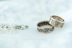 Ślubni złociści pierścionki na białym faborku Zdjęcie Stock