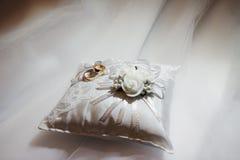 Ślubni złociści pierścionki na prezenta bielu poduszce Obraz Royalty Free