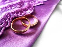 Ślubni złociści pierścionki na purpurowej i białej tkaninie Obraz Stock