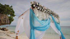 Ślubny łuk dekorował z kwiatami i ampułą rozwija tkaniny na tropikalnej plaży Filipiny Bohol zbiory