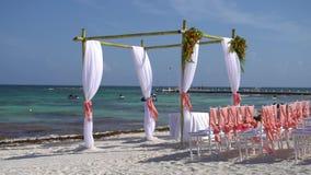 Ślubny łuk dekorował z kwiatami i ampułą rozwija tkaniny na tropikalnej plaży Turkus woda zbiory wideo