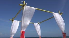 Ślubny łuk dekorował z wielkimi rozwija tkaninami na tropikalnej plaży Turkus woda morze karaibskie zbiory