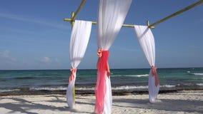 Ślubny łuk dekorował z wielkimi rozwija tkaninami na tropikalnej plaży Turkus woda morze karaibskie zdjęcie wideo