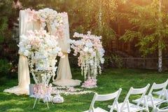 Ślubny łuk dekorujący z płótnem i kwiatami outdoors Piękny ślubu ustawianie Ślubna ceremonia na zielonym gazonie w obrazy stock