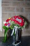 Ślubny bridal bukiet w czarnym plastikowym wiadrze na tle ściana Fotografia Stock