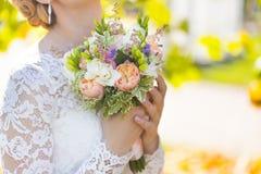 Ślubny bukiet biel i fiołek kwitnie w rękach panna młoda lub kobieta Zdjęcia Stock