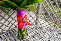 Ślubny bukiet i dekoracja czerwone róże kwitną na łozinowym meblarskim fotelu dla panna młoda fornala Szczegóły poślubiają dzień Fotografia Royalty Free