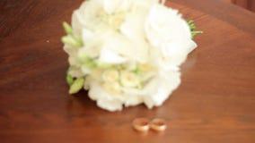 Ślubny bukiet i obrączki ślubne na stole zbiory