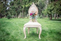 Ślubny bukiet na krześle po środku lasu Obrazy Royalty Free