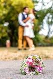 Ślubny bukiet przed nowożeńcy dobiera się tło, całowanie Płytkiej głębii bokeh zdjęcia stock