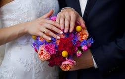 Ślubny bukiet różowe róże, błękit, czerwień, kolor żółty kwitnie i ręki państwo młodzi Obrazy Stock