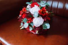 Ślubny bukiet z czerwonymi i białymi kwiatami stoi na czerwonym krześle zdjęcia stock