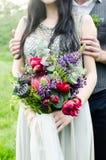 Ślubny bukiet z kwiatami i białym faborkiem zieleni, czerwieni i fiołka, Państwo młodzi z ślubnym bukietem w ona ręki Fotografia Royalty Free