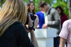 Ślubny fotograf w trakcie jego pracy Fachowy fotograf strzela ślubną ceremonię Młodej dziewczyny spojrzenia w obraz stock