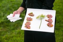 Ślubny organizator przyjęć niesie talerza jedzenie obraz stock