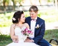 Ślubny państwo młodzi na ławce z natura krajobrazu scenerii tłem Zdjęcie Royalty Free