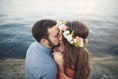 Ślubny pary obsiadanie na ampuła kamieniu wokoło błękitnego morza Obrazy Stock
