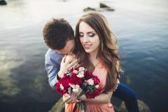 Ślubny pary obsiadanie na ampuła kamieniu wokoło błękitnego morza Zdjęcie Stock