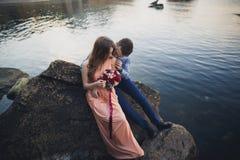 Ślubny pary obsiadanie na ampuła kamieniu wokoło błękitnego morza Obraz Stock