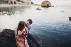 Ślubny pary obsiadanie na ampuła kamieniu wokoło błękitnego morza Zdjęcie Royalty Free