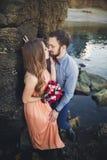 Ślubny pary obsiadanie na ampuła kamieniu wokoło błękitnego morza Obrazy Royalty Free