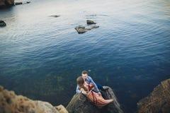 Ślubny pary obsiadanie na ampuła kamieniu wokoło błękitnego morza Zdjęcia Royalty Free