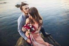 Ślubny pary obsiadanie na ampuła kamieniu wokoło błękitnego morza Fotografia Stock