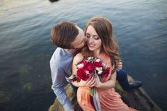 Ślubny pary obsiadanie na ampuła kamieniu wokoło błękitnego morza Fotografia Royalty Free