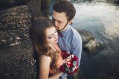 Ślubny pary obsiadanie na ampuła kamieniu wokoło błękitnego morza Zdjęcia Stock