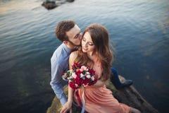 Ślubny pary obsiadanie na ampuła kamieniu wokoło błękitnego morza Obraz Royalty Free
