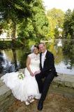 Ślubny pary obsiadanie przy smal stawem w jesień Fotografia Royalty Free