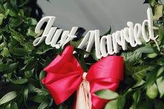 Ślubny rocznika wianek z Właśnie Zamężnym tekstem z czerwonym faborkiem Zdjęcie Royalty Free