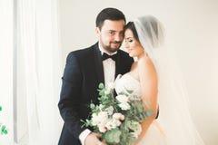 Ślubny sesja zdjęciowa. nowożeńcy dobiera się w pięknym hotelu pozuje blisko okno zdjęcia royalty free