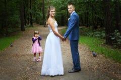 Ślubny spacer, nowożeńcy z dziecka odprowadzeniem w lesie zdjęcie stock