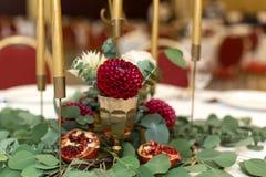 Ślubny stołowy położenie dekoruje z świeżymi kwiatami w mosiężnym pucharze złotych świeczkach w mosiężnych candlesticks i _ zdjęcie royalty free