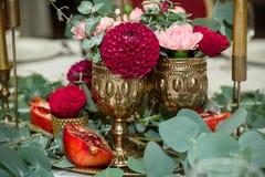 Ślubny stołowy położenie dekoruje z świeżymi kwiatami w mosiężnym pucharze złotych świeczkach w mosiężnych candlesticks i _ zdjęcia stock