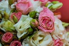Ślubny złocisty pierścionek Romantyczni dwa zobowiązania diamentowi pierścionki są na panna młoda bukiecie różowi róż i białych k obraz stock