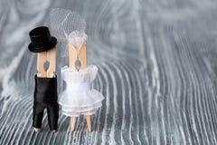 Ślubny zaproszenie karty szablon Clothespins Przygotowywają w czarnej kostiumu i panny młodej bielu sukni na szarym drewnianym tl Obrazy Stock