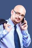 Śmiały głowiasty facet z szkłami robi rozmowie telefonicza fotografia stock